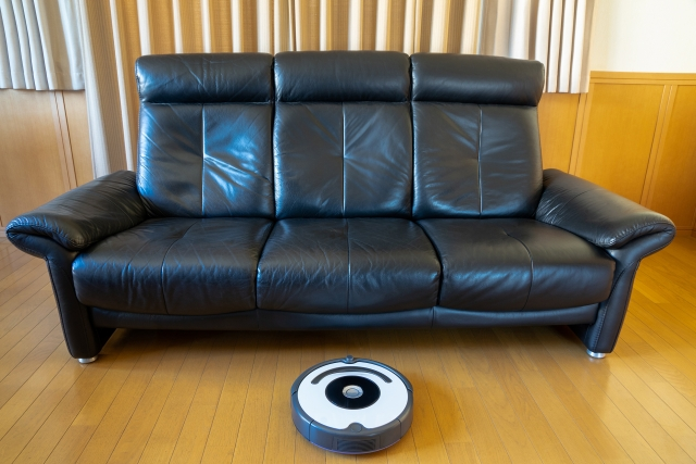 ソファーの下へ潜ろうとするロボット掃除機